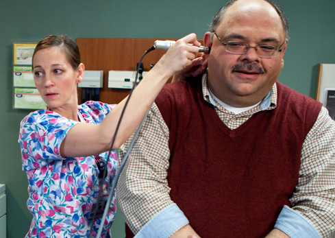 Veteran receiving ear test from primary care provider.